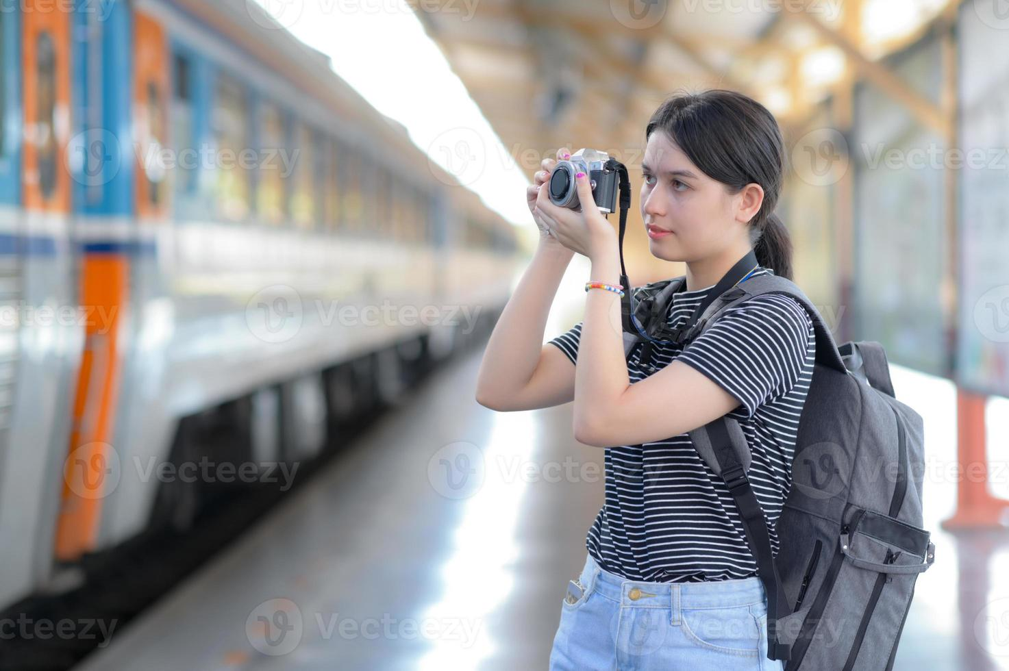 enquanto espera o trem, uma jovem visitante estrangeira carrega uma câmera para tirar fotos. foto