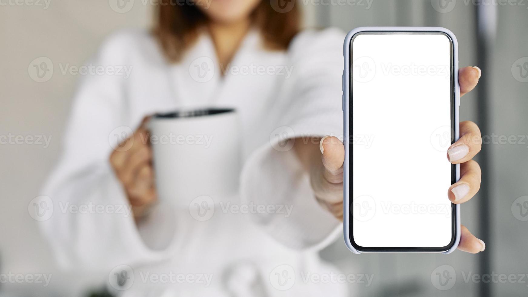 mulher mostrando telefone em branco foto