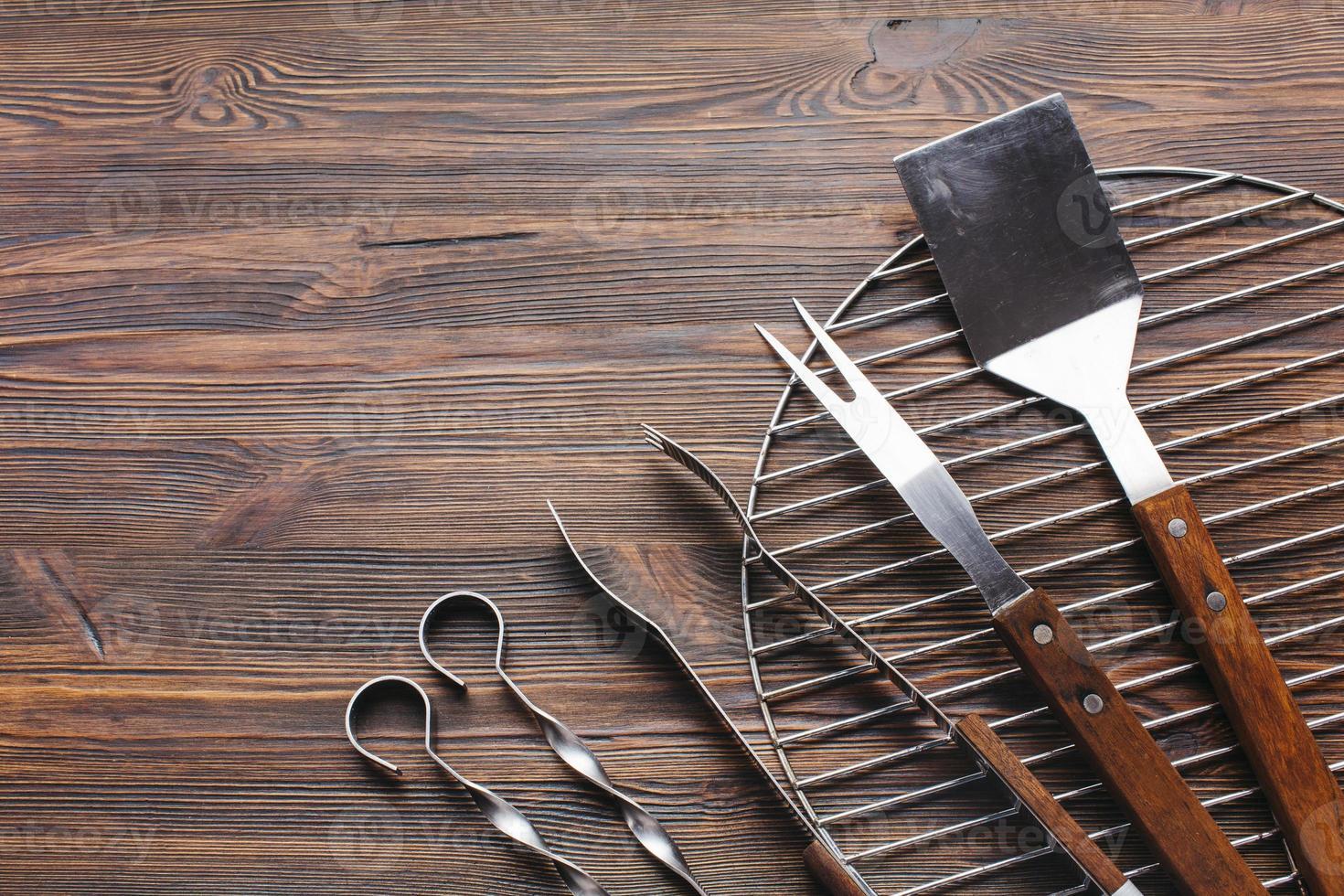Novos utensílios de churrasco metálico fundo de madeira foto