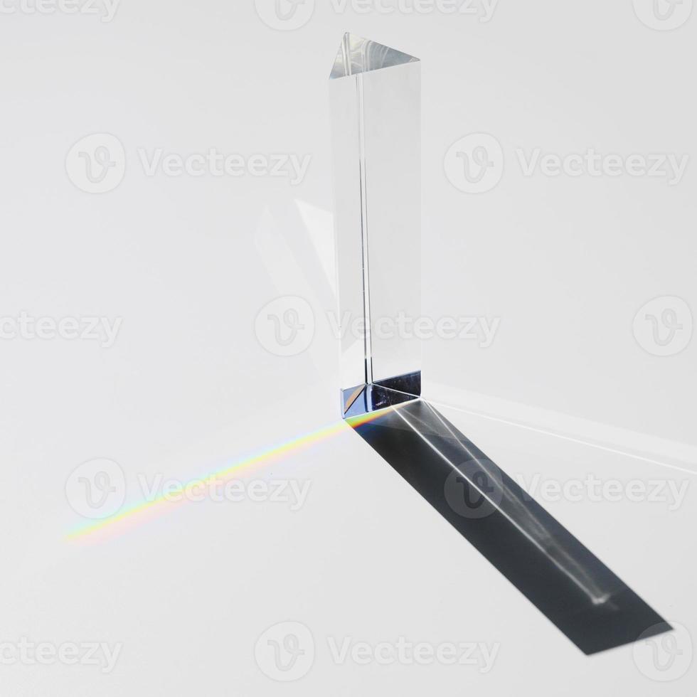 prisma dividindo a luz do sol em espectro no fundo branco foto