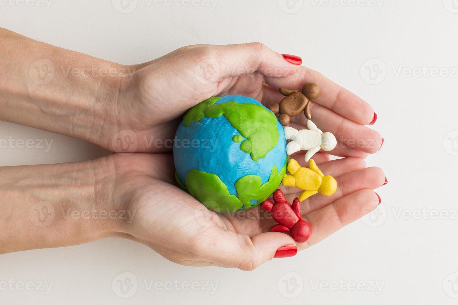 mãos segurando um pequeno globo e figuras de pessoas foto
