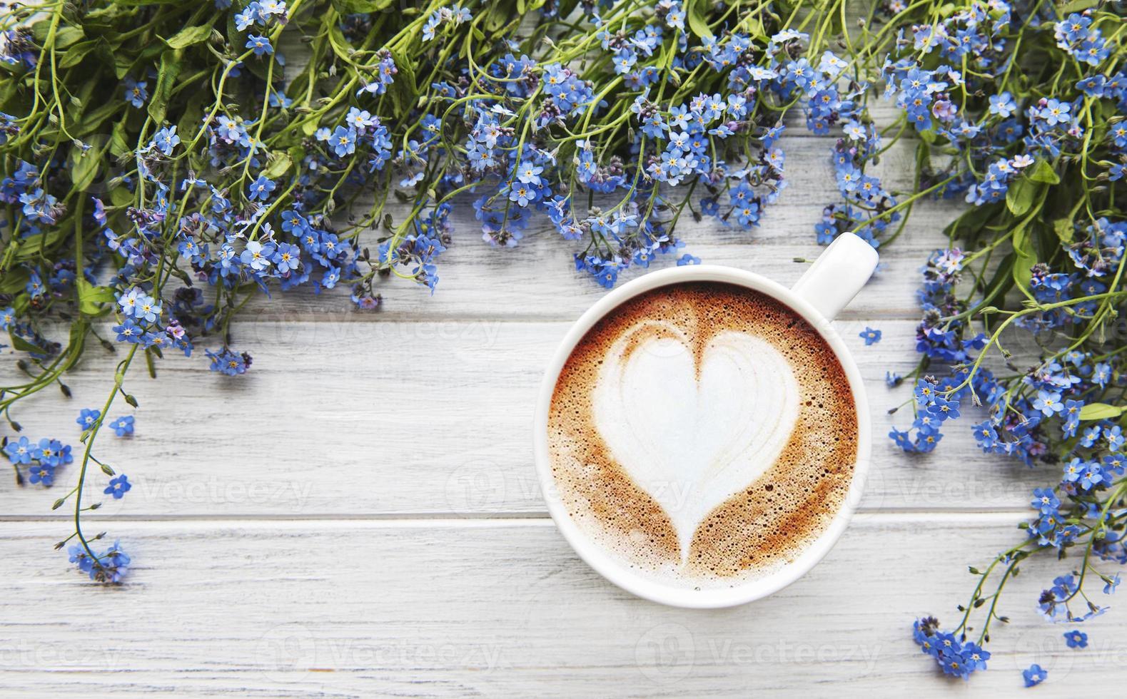 flores não-me-esqueças e xícara de café em um fundo de madeira foto
