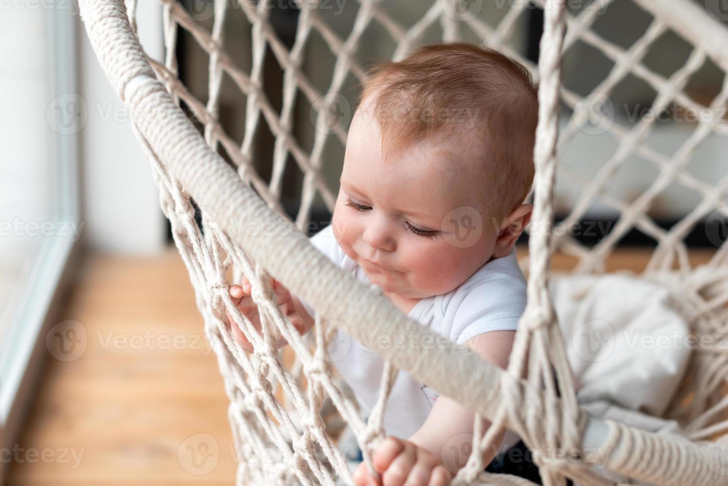 menina bonitinha em um balanço de cadeira de tricô foto