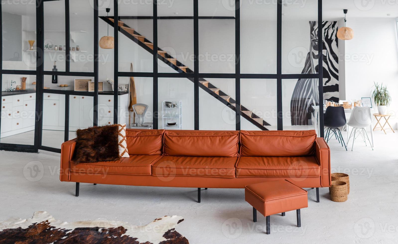 apartamento estiloso, espaço aberto, no meio da sala está um sofá bonito e moderno foto