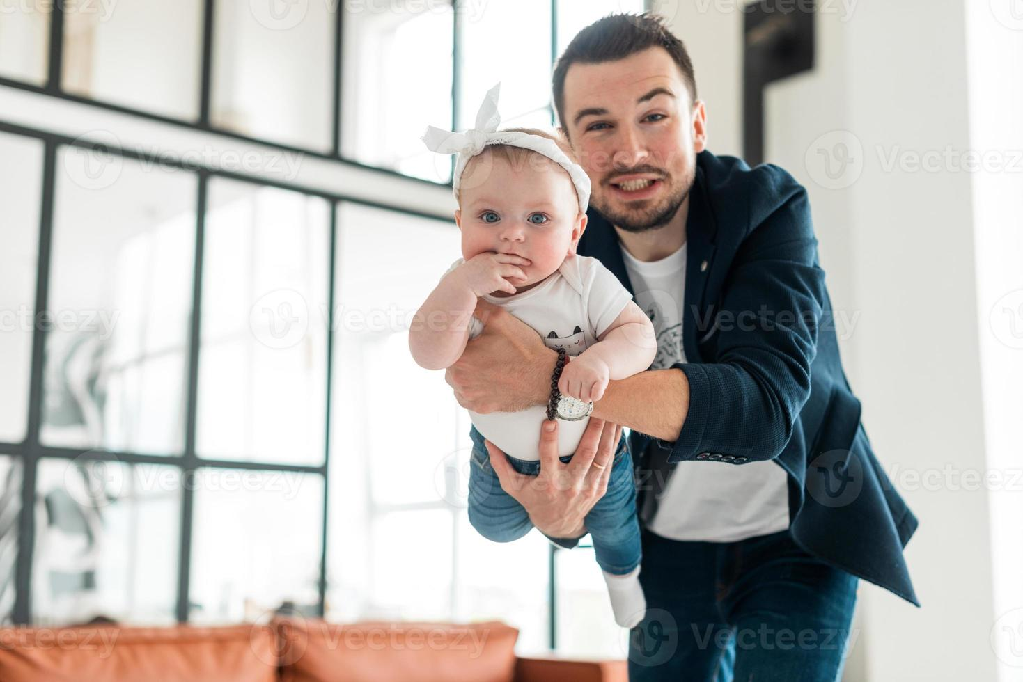homem bonito e sorridente, segurando sua amada filha. parece que uma criança está voando foto