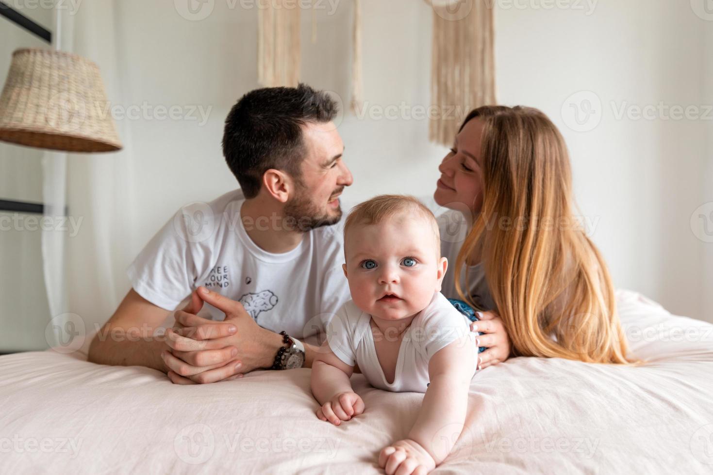 família feliz, mãe, pai e filha em uma cama branca em um quarto ensolarado. pais e uma criança pequena estão descansando em casa. foto