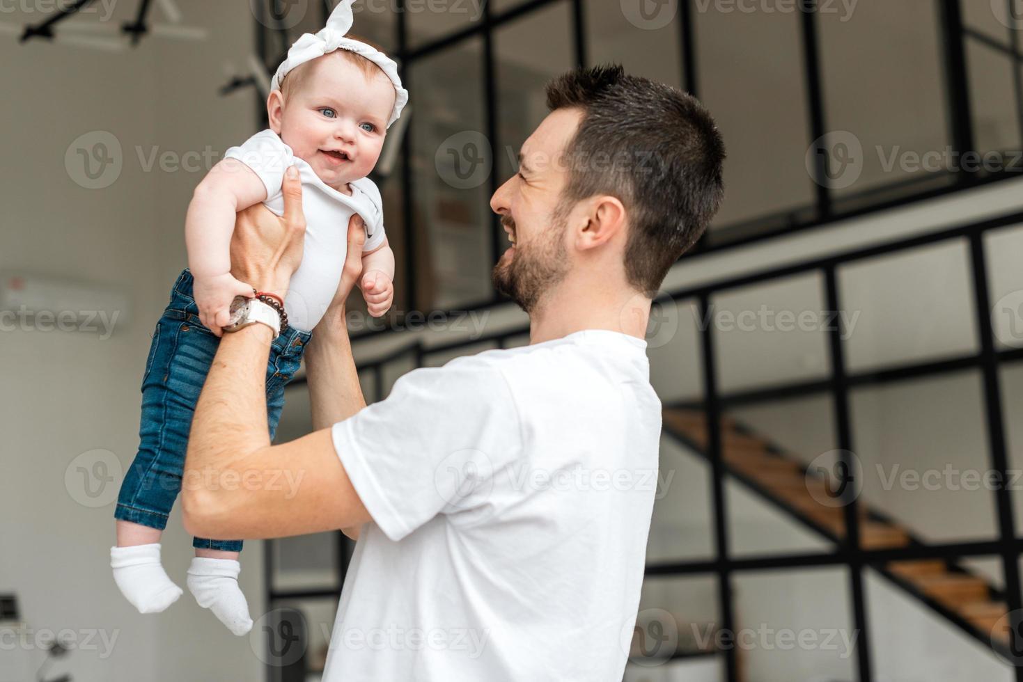 um jovem segura sua filhinha. menina sorrindo feliz foto