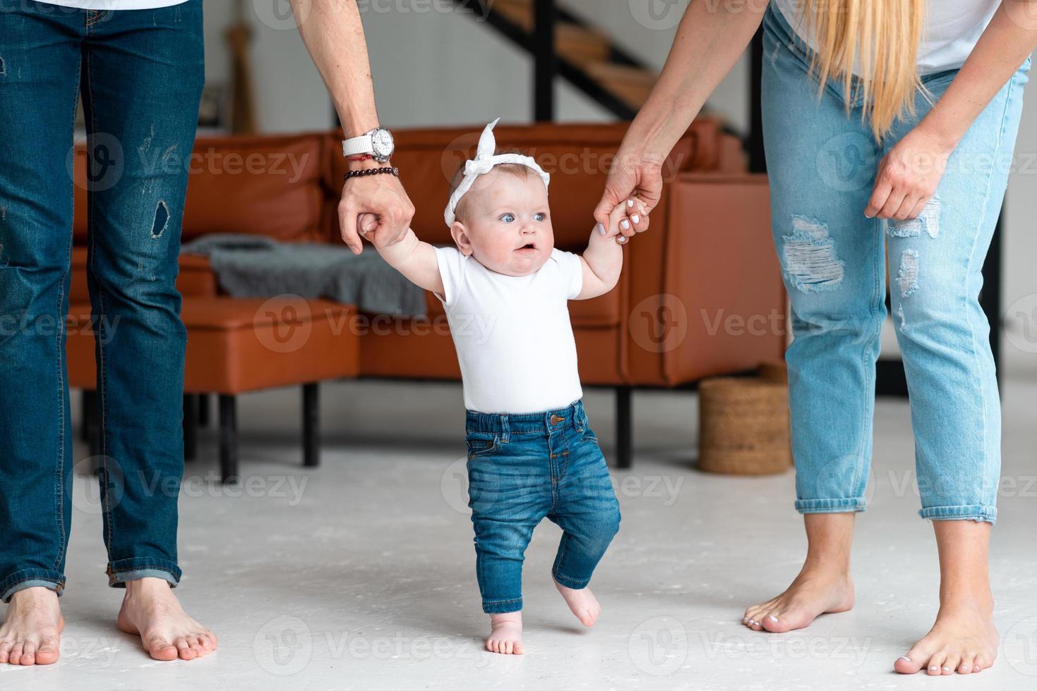 pais seguram uma filhinha fofa pelas alças, ensinam-na a andar foto