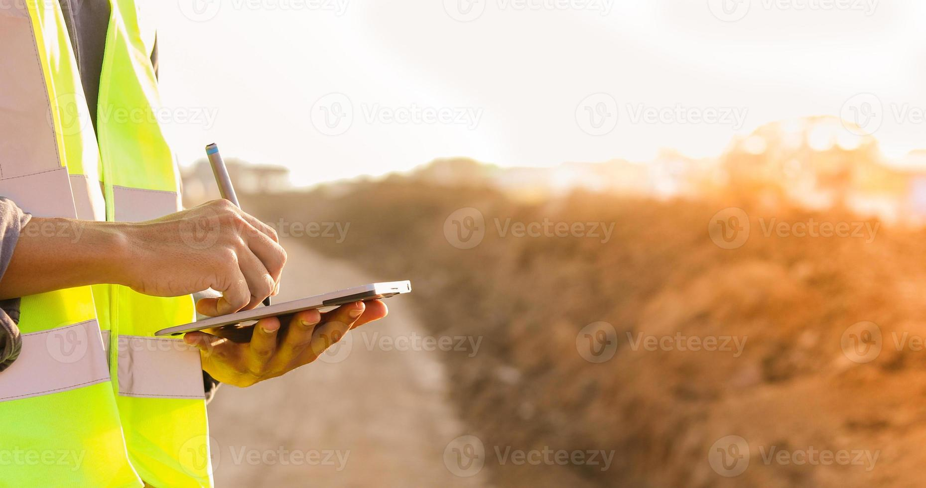 engenheiro asiático com capacete de segurança usando computador tablet pc inspecionando e trabalhando no canteiro de obras foto