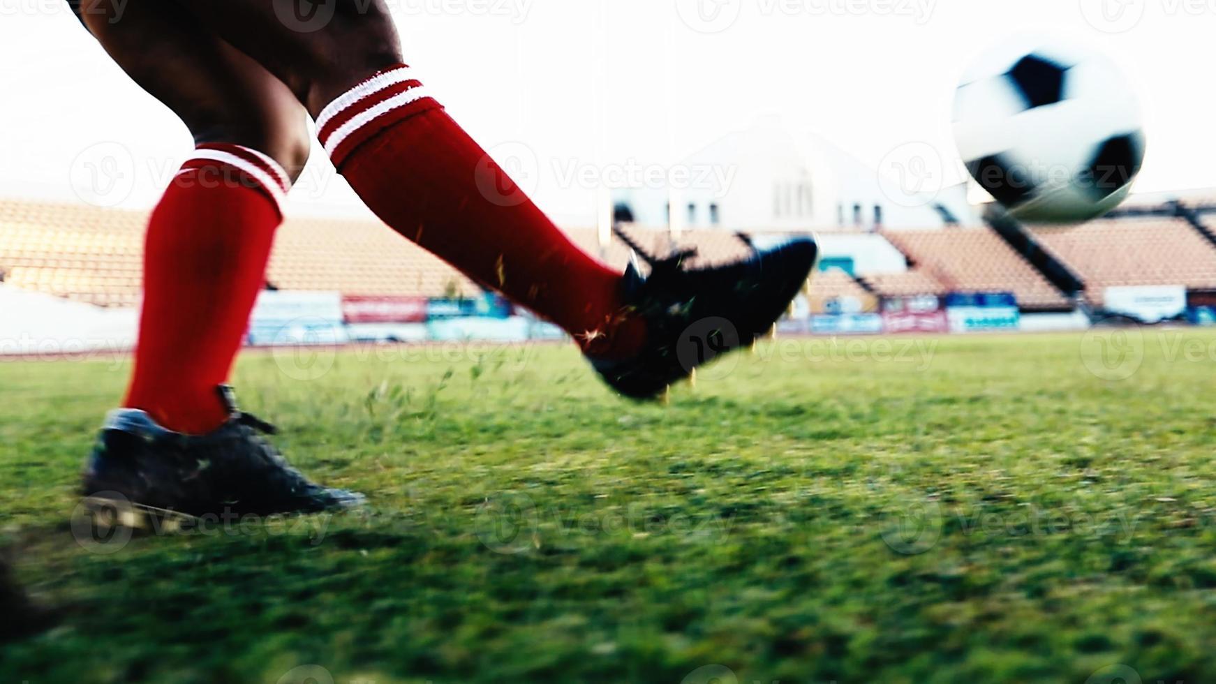 jogador de futebol ou futebol americano em pé com a bola no campo para chutar a bola no estádio de futebol foto