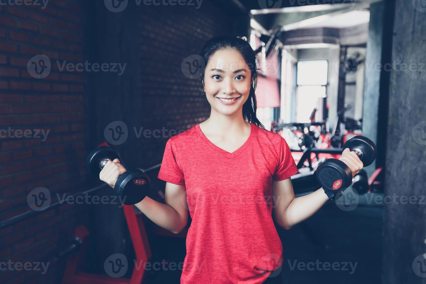 linda musculoso apto mulher exercitando construção de músculos e fitness mulher fazendo exercícios no ginásio. fitness - conceito de estilo de vida saudável foto