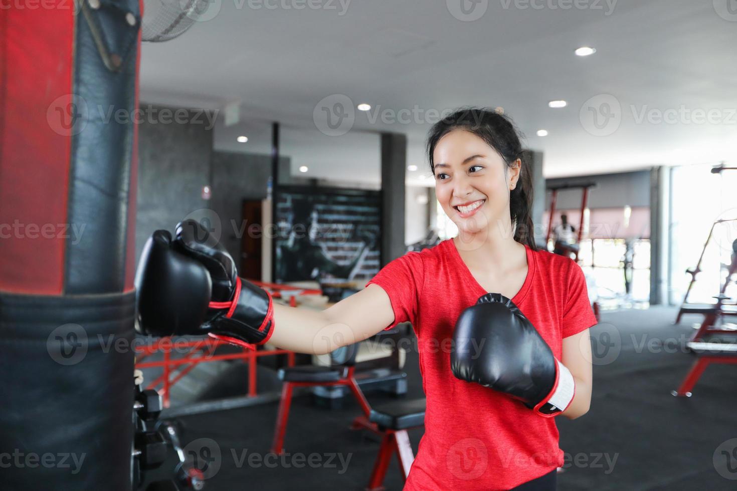 mulheres bonitas boxer asiático feliz e divertido fitness boxe e socar um saco com o uso de luvas de boxe. foto