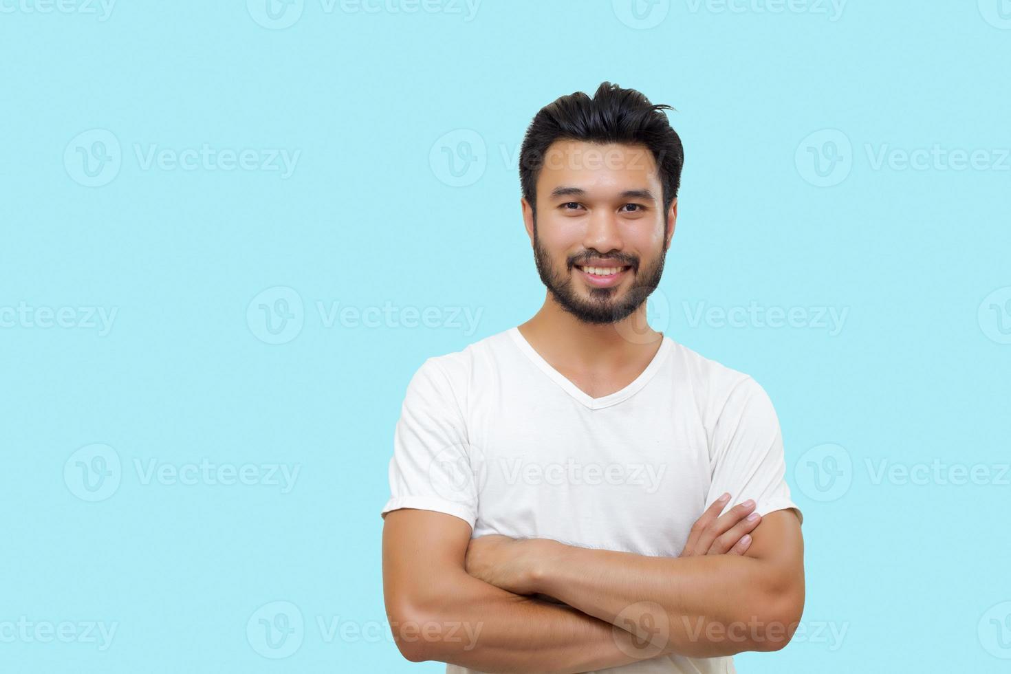 homem bonito asiático com bigode, sorrindo e rindo, isolado no fundo azul foto