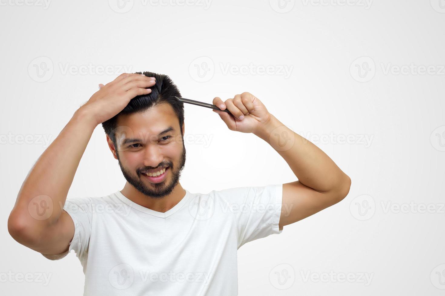 conceito de pessoas - jovem sorridente, escovando o cabelo com o pente no fundo branco foto