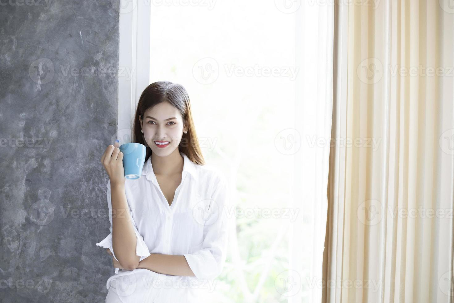 mulheres asiáticas tomando café e acordando em sua cama totalmente descansadas e abrindo as cortinas pela manhã para tomar ar fresco no sol foto