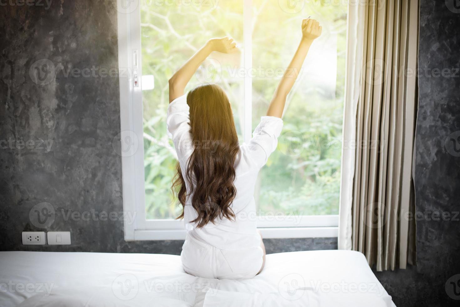 mulher asiática linda jovem sorridente mulher sentada na cama e alongamento pela manhã no quarto, depois de acordar em sua cama totalmente descansada e abrir as cortinas pela manhã para tomar ar fresco. foto