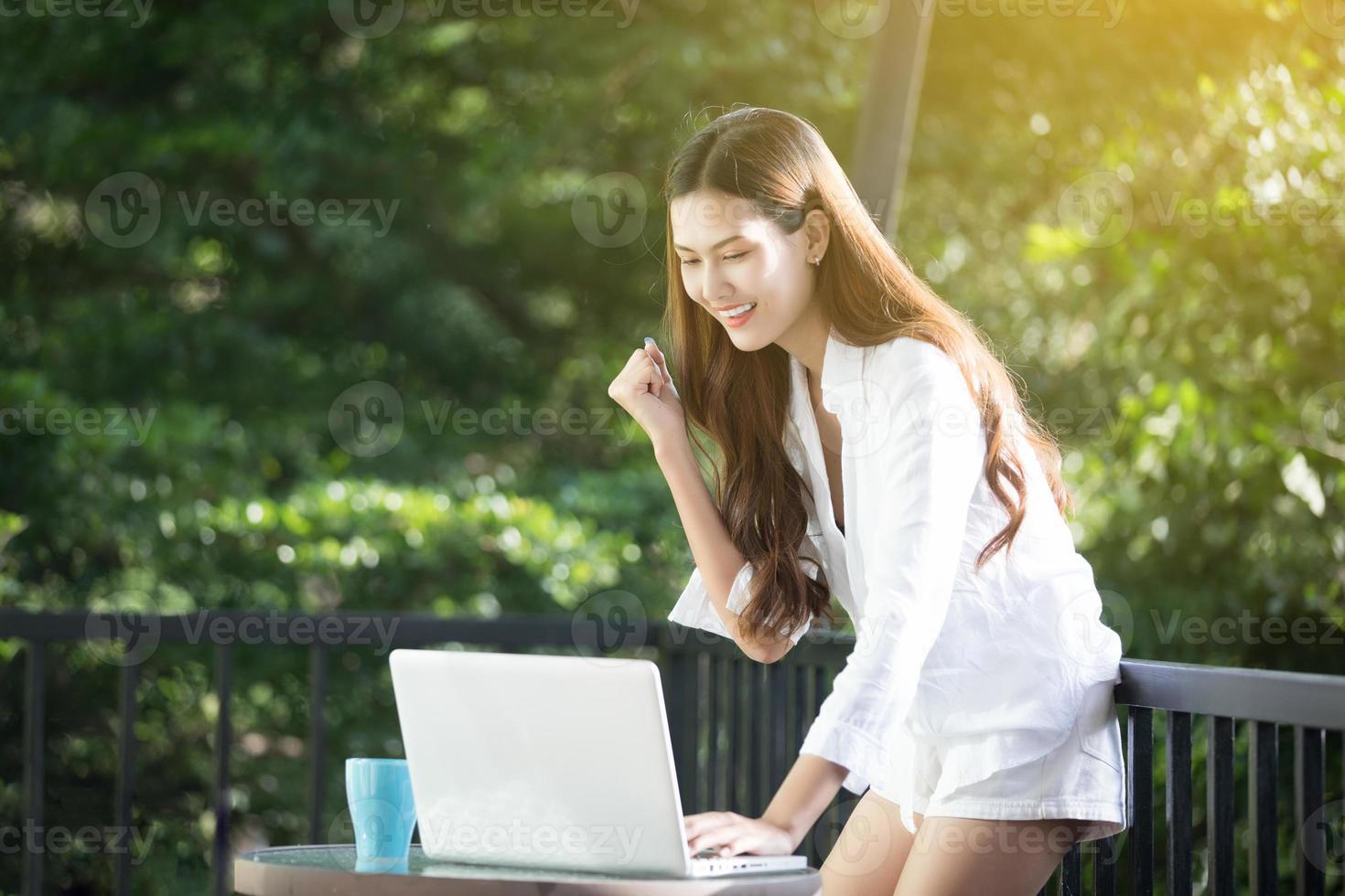 Mulher de negócios asiáticos arma-se para celebrar o sucesso trabalhando, conceito de sucesso foto