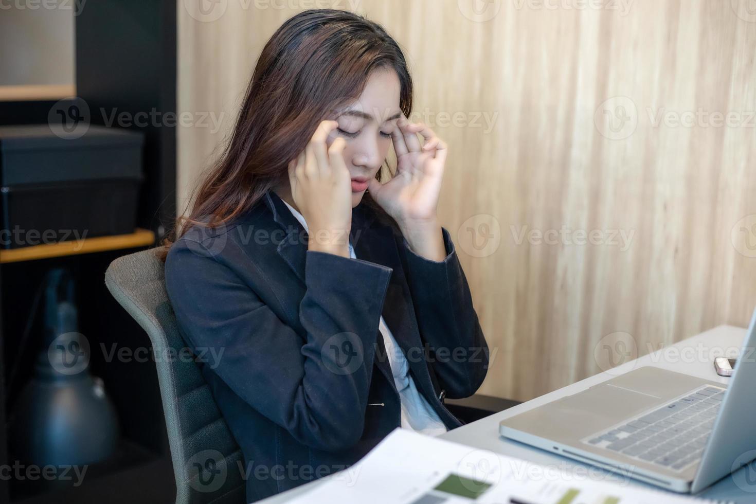 empresária asiática falando sério sobre o trabalho árduo feito até a dor de cabeça foto