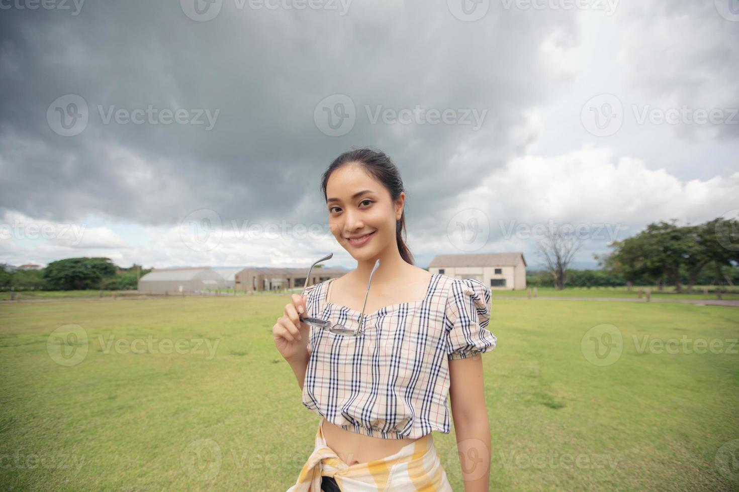 em pé mulher segurando óculos escuros e sorrindo feliz no parque. foto