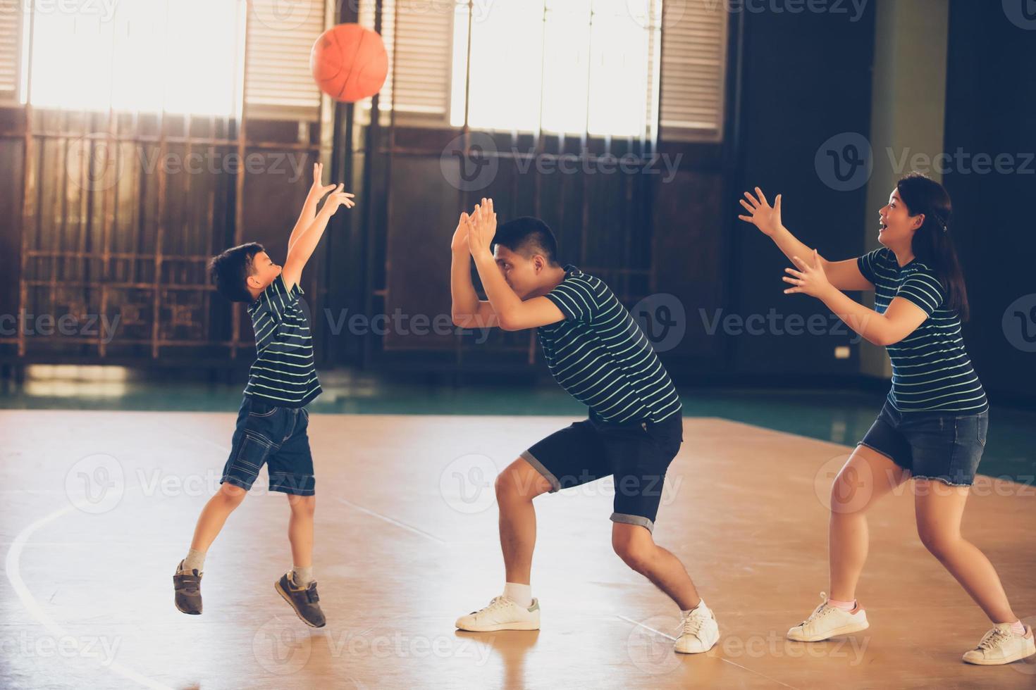 família asiática jogando basquete juntos. família feliz passando tempo livre junta nas férias foto
