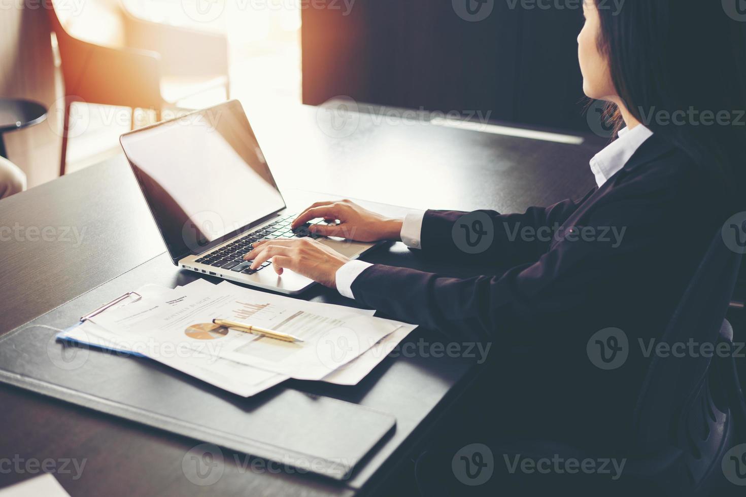 Mulheres de negócios asiáticas usando documentos de análise de computador laptop e diagrama financeiro gráfico na mesa do escritório trabalhando foto