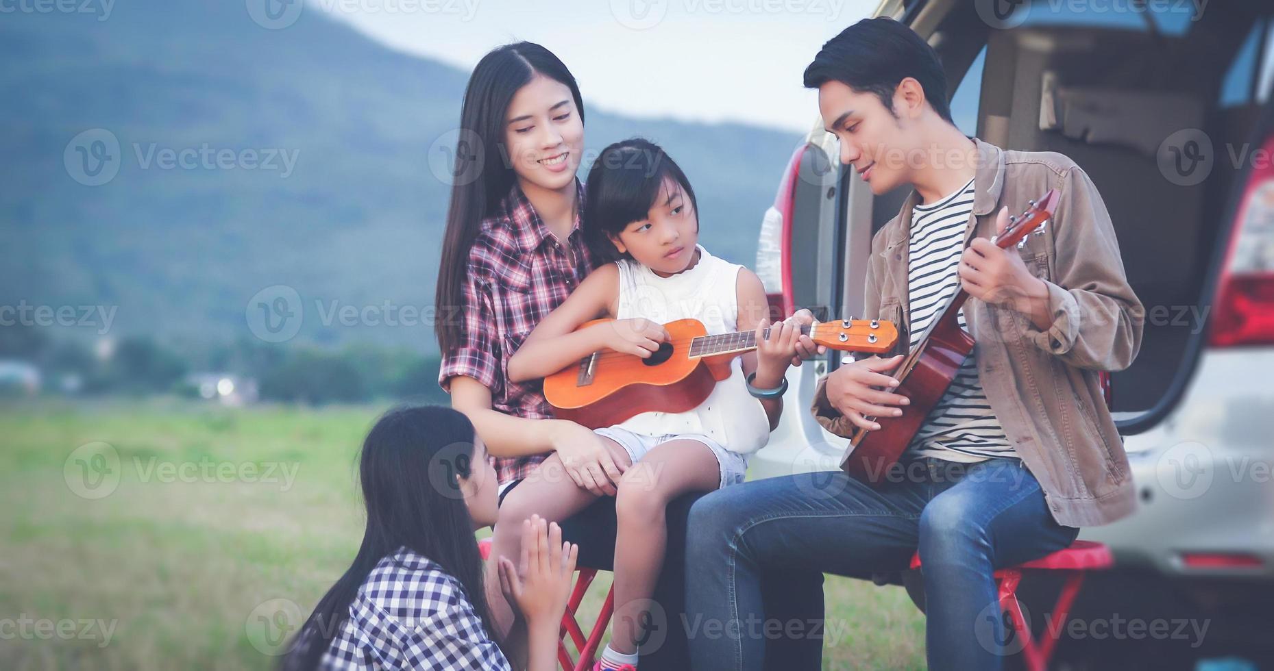 menina feliz tocando cavaquinho com uma família asiática sentada no carro para aproveitar a viagem e as férias de verão foto
