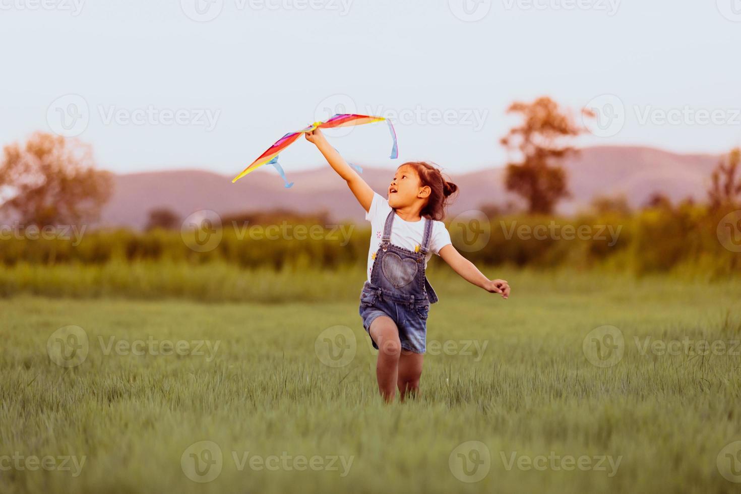 filha asiática e pai com uma pipa correndo e feliz no prado no verão na natureza foto