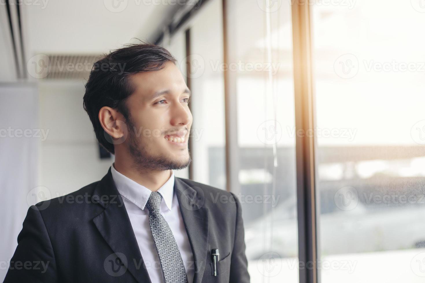empresário bonito feliz em pé e sorrindo no escritório foto