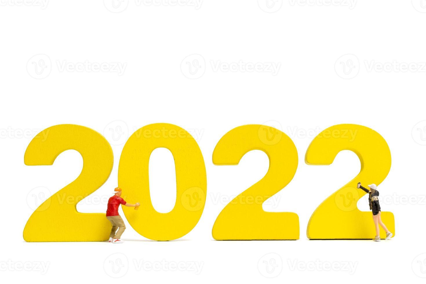 adolescentes em miniatura pintando a tinta número 2022 em fundo branco foto