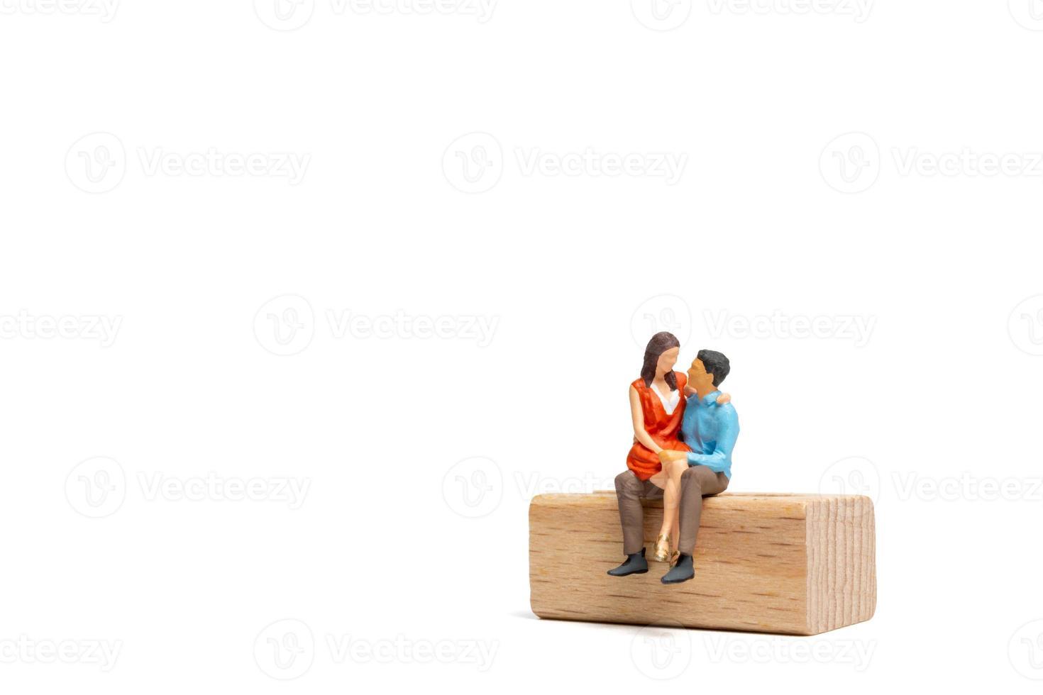 casal de pessoas em miniatura sentado em uma cadeira de madeira e espaço para o tex foto