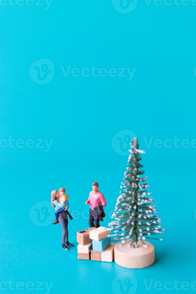 pessoas em miniatura, família feliz ao lado de uma árvore de natal foto