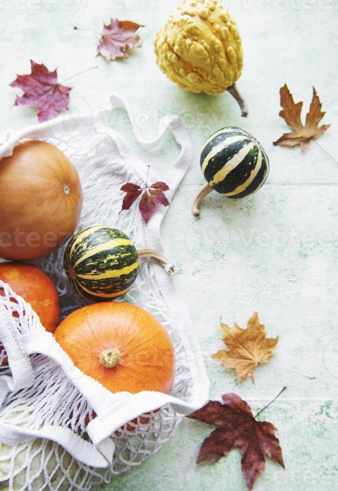 composição de outono com várias abóboras em uma sacola ecológica foto