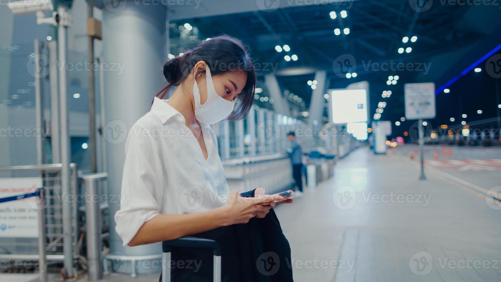 garota de negócios asiática chegar destino usar máscara facial ficar do lado de fora olhar terminal de carro de espera de telefone inteligente no aeroporto doméstico. pandemia de covid de viajante de negócios, conceito de distanciamento social de viagens de negócios. foto