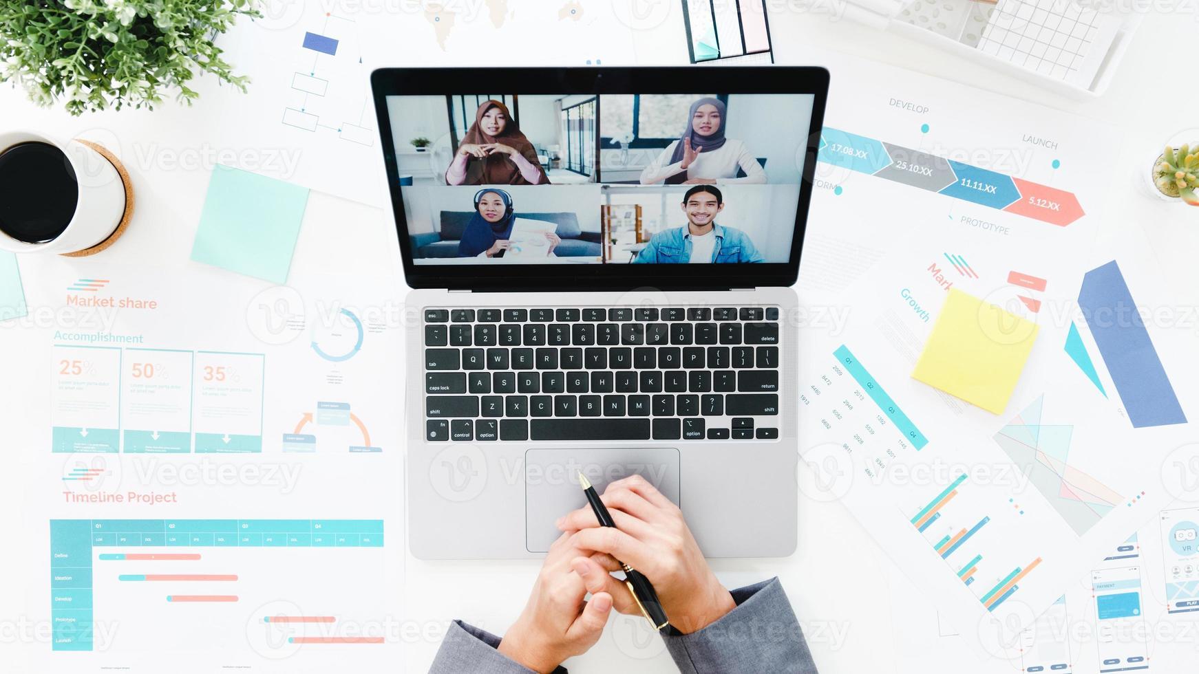vista superior da jovem empresária asiática usando laptop conversa com um colega sobre o plano de uma reunião de videochamada enquanto trabalha em casa na sala de estar. distanciamento social, quarentena para prevenção do vírus corona. foto