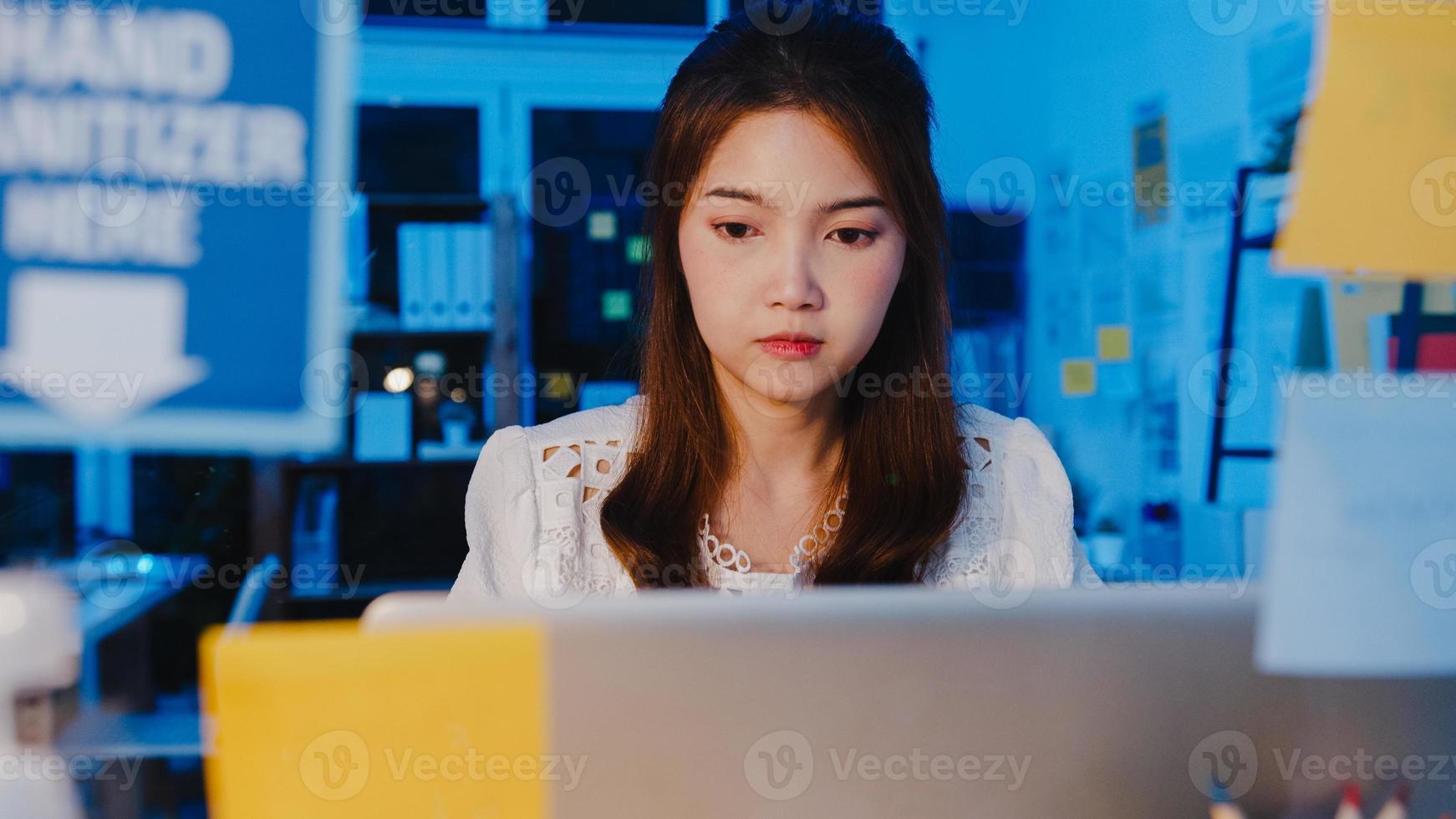 mulheres asiáticas freelance usando laptop trabalham duro no novo escritório doméstico normal. trabalho em casa sobrecarregada à noite, trabalho remoto, auto-isolamento, distanciamento social, quarentena para prevenção do vírus corona. foto