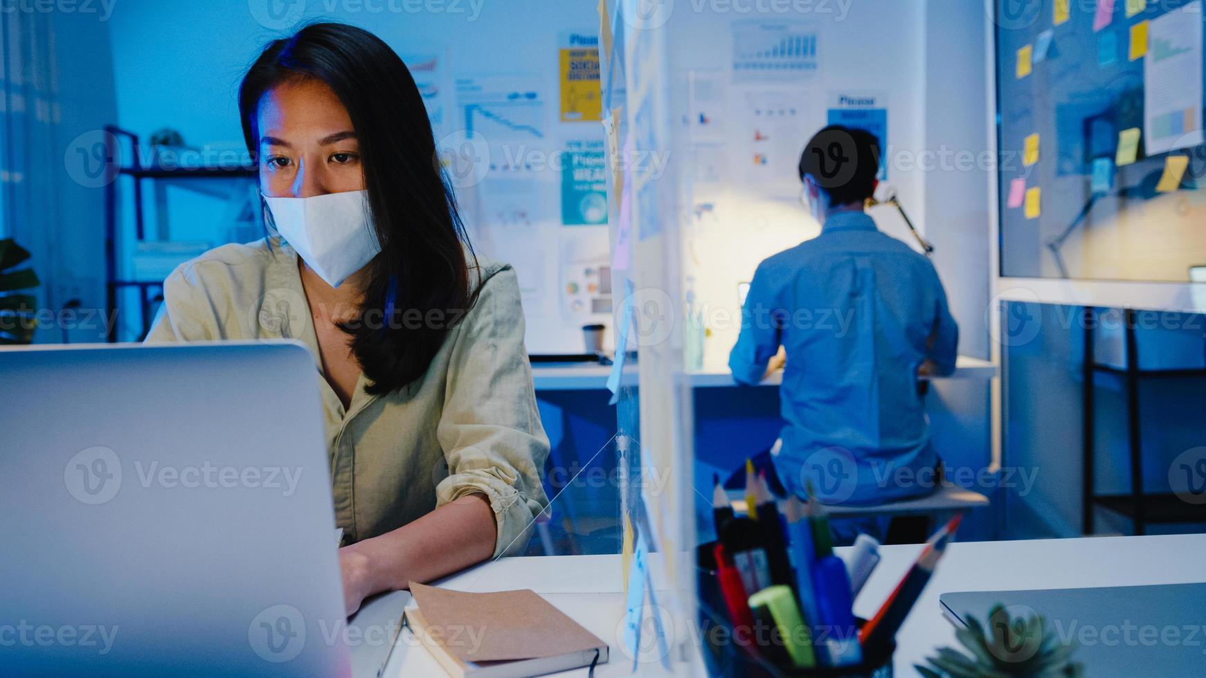 feliz empresária asiática usando máscara médica para distanciamento social em uma nova situação normal para prevenção de vírus enquanto usa o laptop no trabalho à noite no escritório. vida e trabalho após o coronavírus. foto