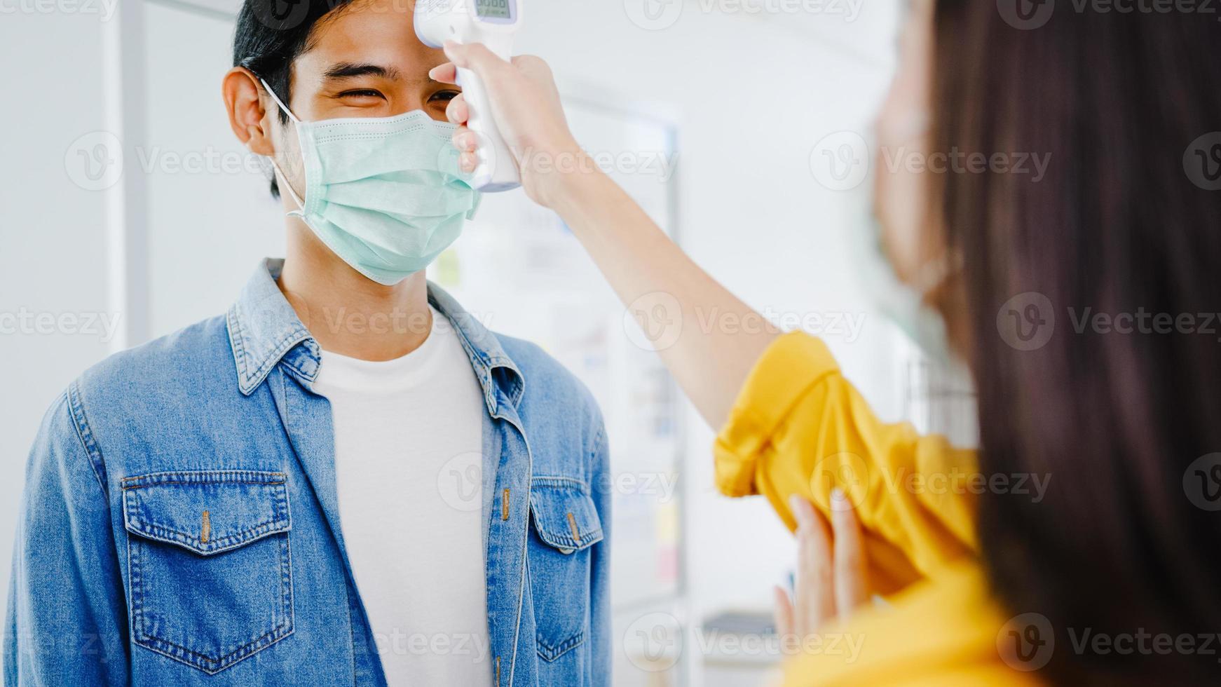 ásia recepcionista conduzindo usar máscara protetora de rosto use verificador de termômetro infravermelho ou pistola de temperatura na testa do cliente antes de entrar no escritório. estilo de vida novo normal após o vírus corona. foto