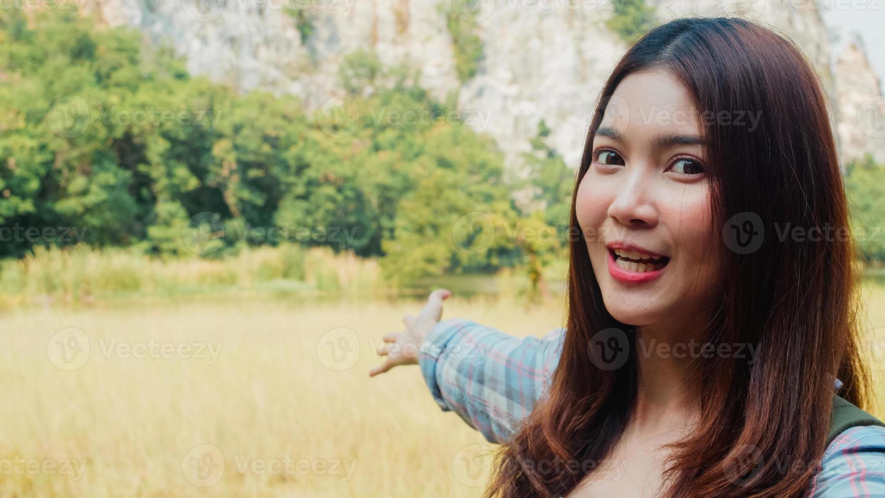 alegre jovem viajante asiática com mochila gravando vídeo vlog com transmissão ao vivo no upload do telefone nas redes sociais no lago da montanha. garota coreana feliz aproveite a viagem de férias. viajar de estilo de vida e relaxar. foto