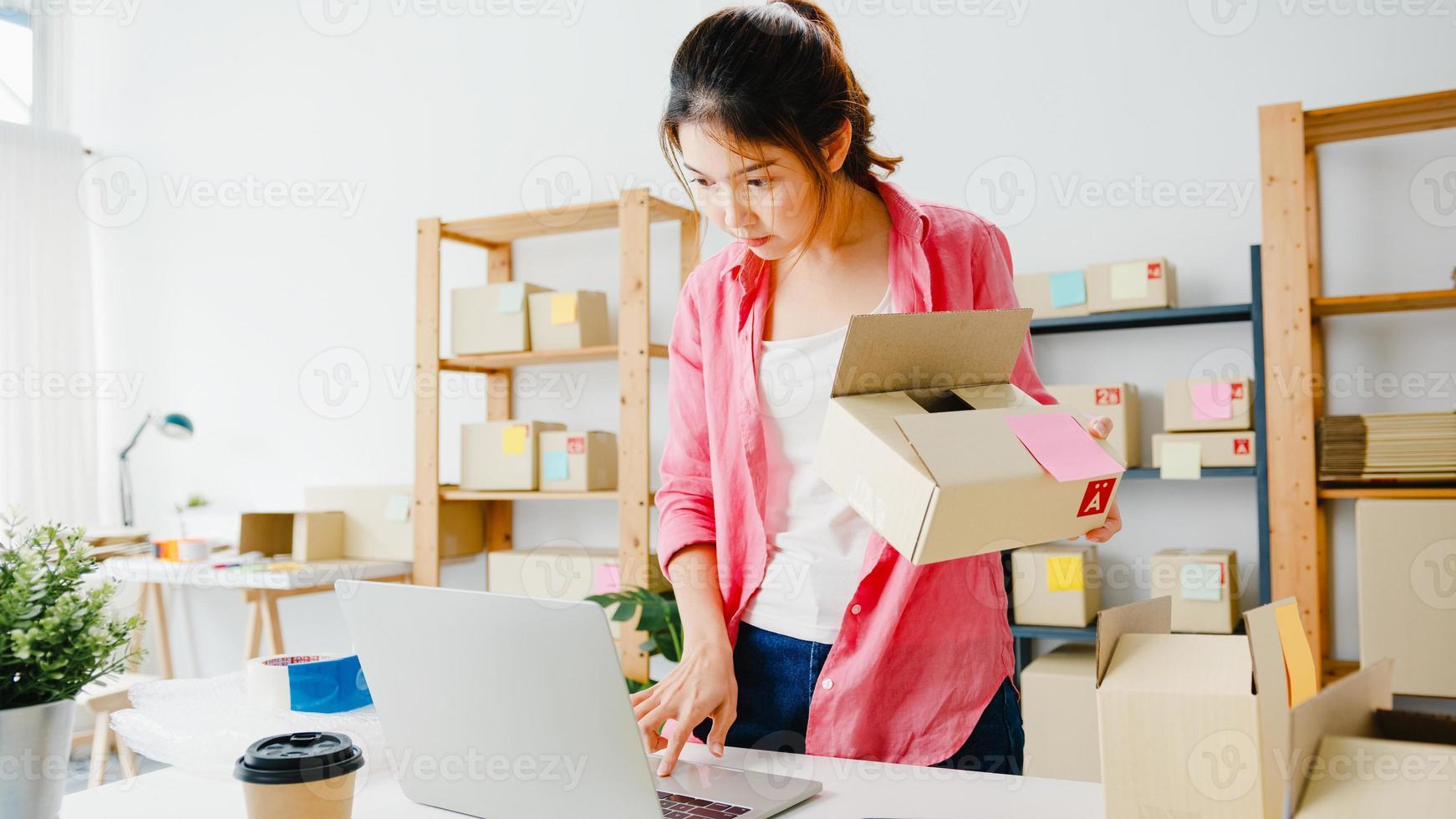 jovem ásia empresário empresária verificar o pedido de compra do produto em estoque e salvar no trabalho do laptop do computador no escritório doméstico. proprietário de uma pequena empresa, entrega de mercado online, conceito freelance de estilo de vida. foto