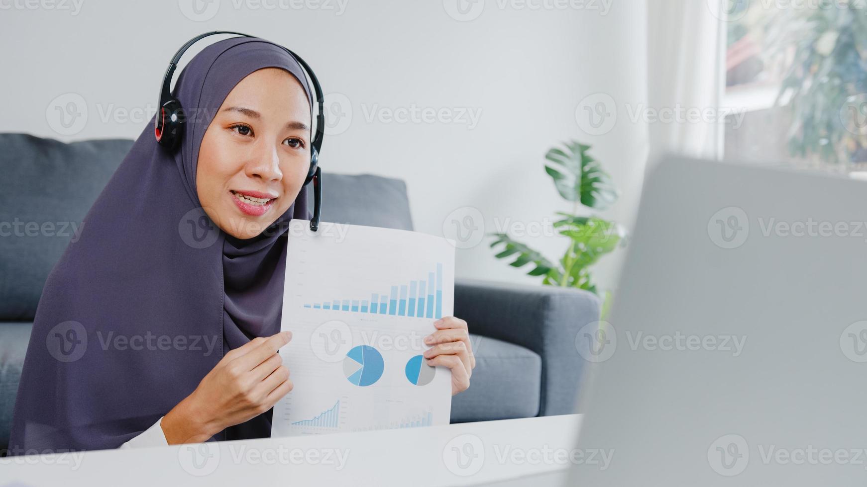 A senhora muçulmana asiática usa fone de ouvido usando laptop e fala com colegas sobre o relatório de venda em uma videoconferência enquanto trabalha em casa na sala de estar. distanciamento social, quarentena para o vírus corona. foto