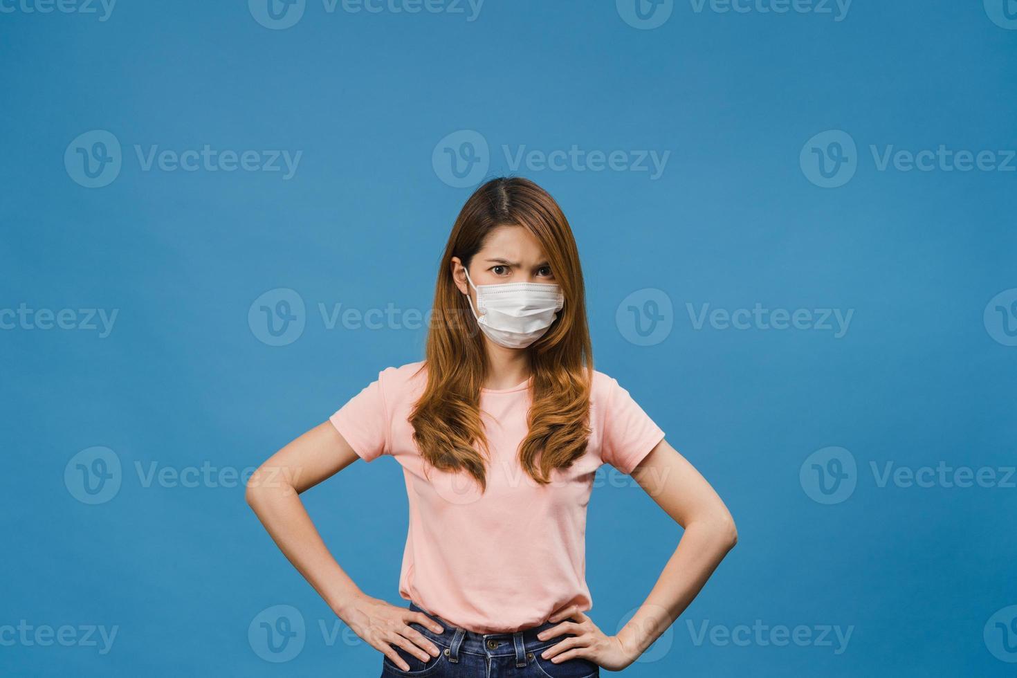jovem asiática usar máscara médica com expressão negativa, grito animado, choro de raiva emocional e olhar para a câmera isolada sobre fundo azul. distanciamento social, quarentena para o vírus corona. foto