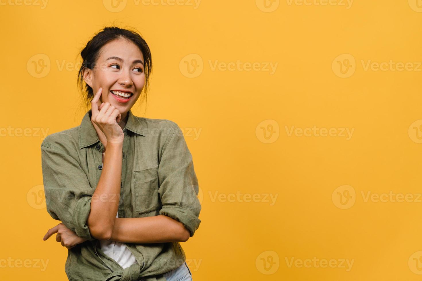 retrato de jovem asiática com expressão positiva, braço cruzado, sorriso amplo, vestido com um pano casual sobre fundo amarelo. feliz adorável feliz mulher alegra sucesso. conceito de expressão facial. foto