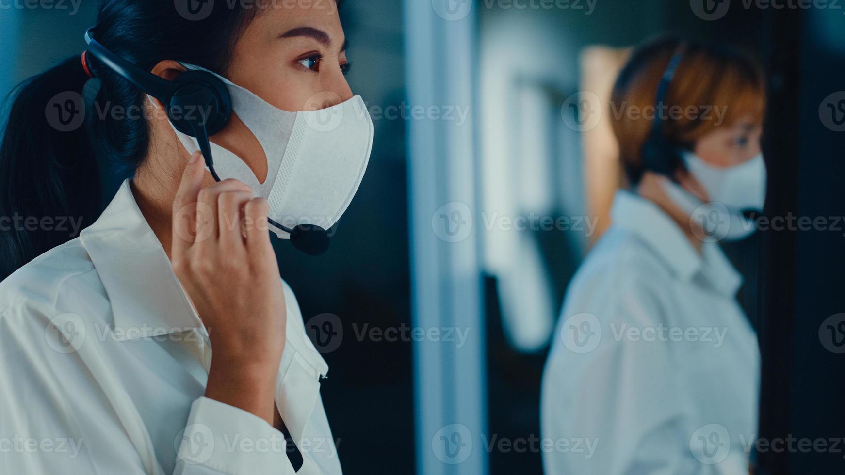 A equipe jovem de call center da Ásia milenar ou executivo de serviço de suporte ao cliente usando máscara facial impede covid-19 usando computador e fone de ouvido com microfone trabalhando no suporte técnico tarde da noite no escritório. foto