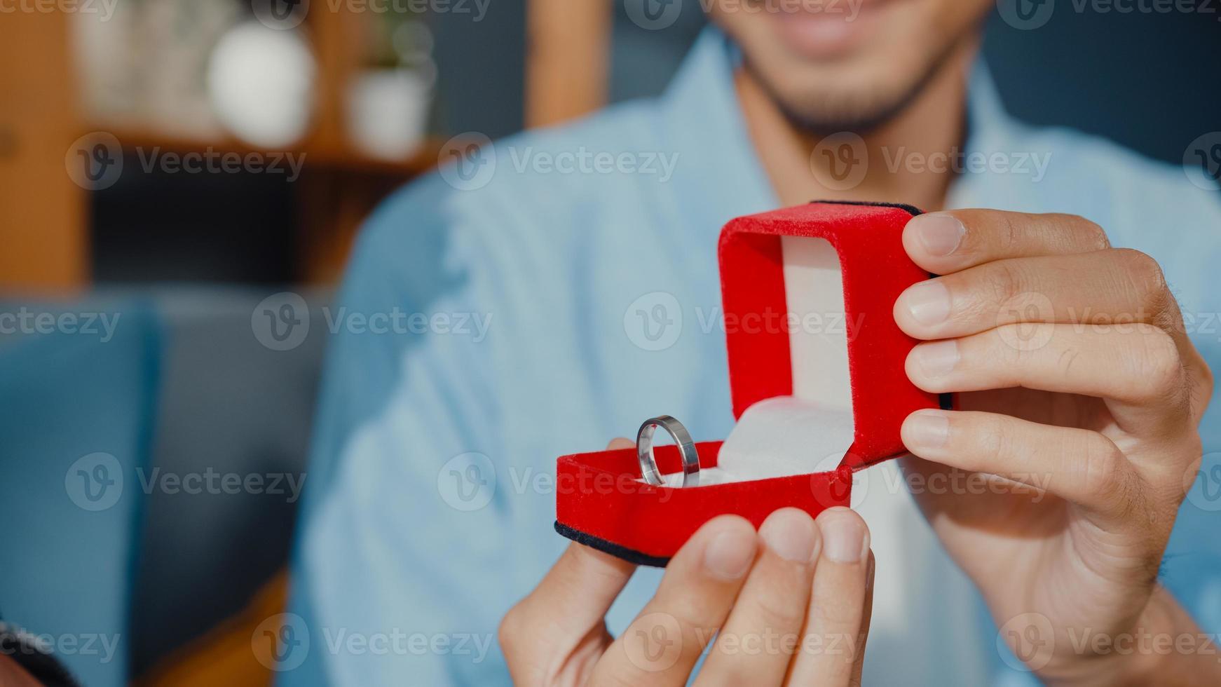 close-up feliz casal asiático homem e mulher sorrindo namorado sentar no sofá surpresa namorada com anel de noivado em caixa vermelha, pedir-lhe uma proposta de casamento em casa. conceito romântico de aniversário. foto