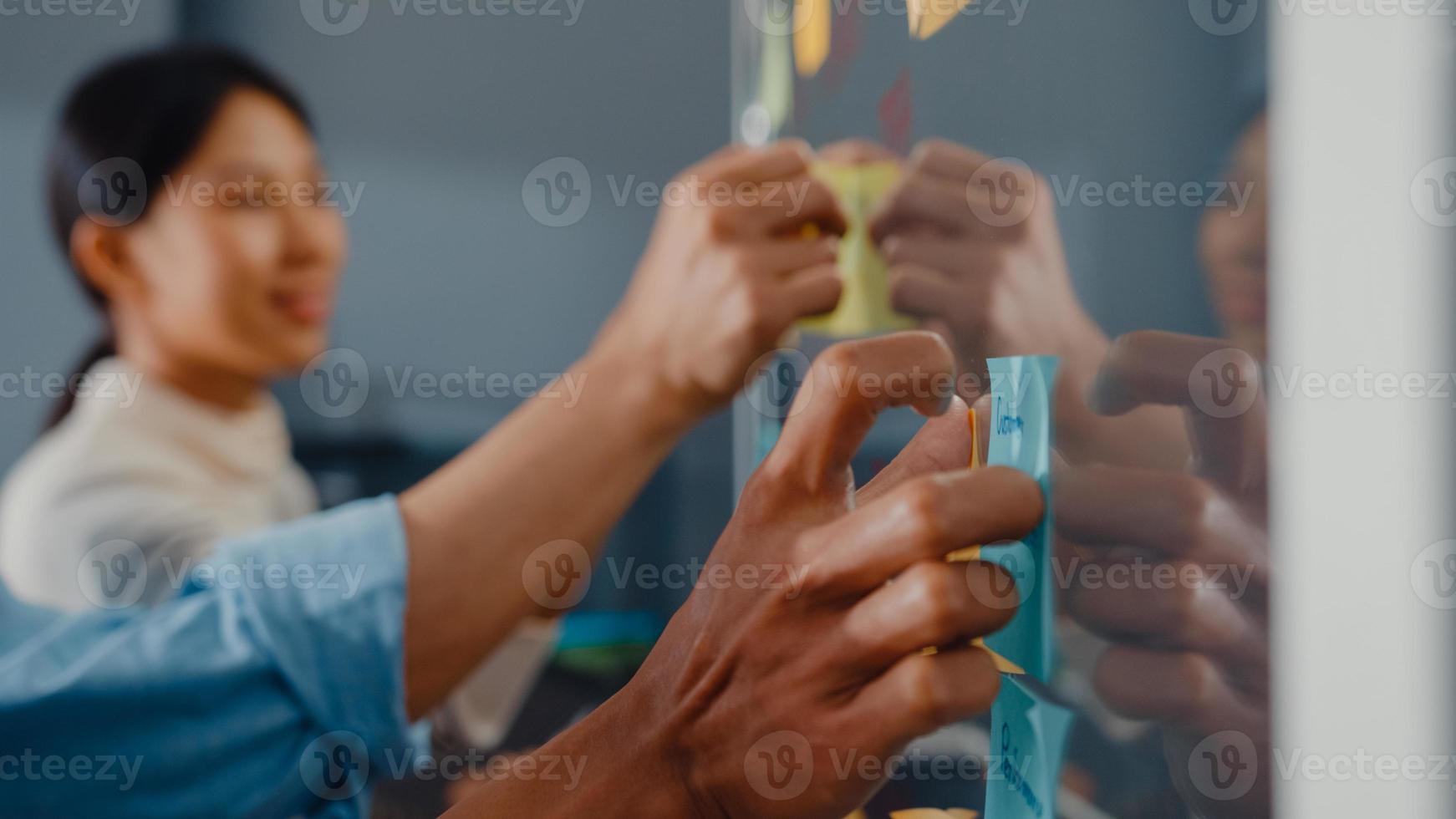 os empresários da ásia ficam atrás da parede de vidro transparente, ouvem o gerente apontando o trabalho do progresso e discutem a reunião e o trabalhador publica nota adesiva na parede do escritório. inspiração de negócios, compartilhe ideias. foto