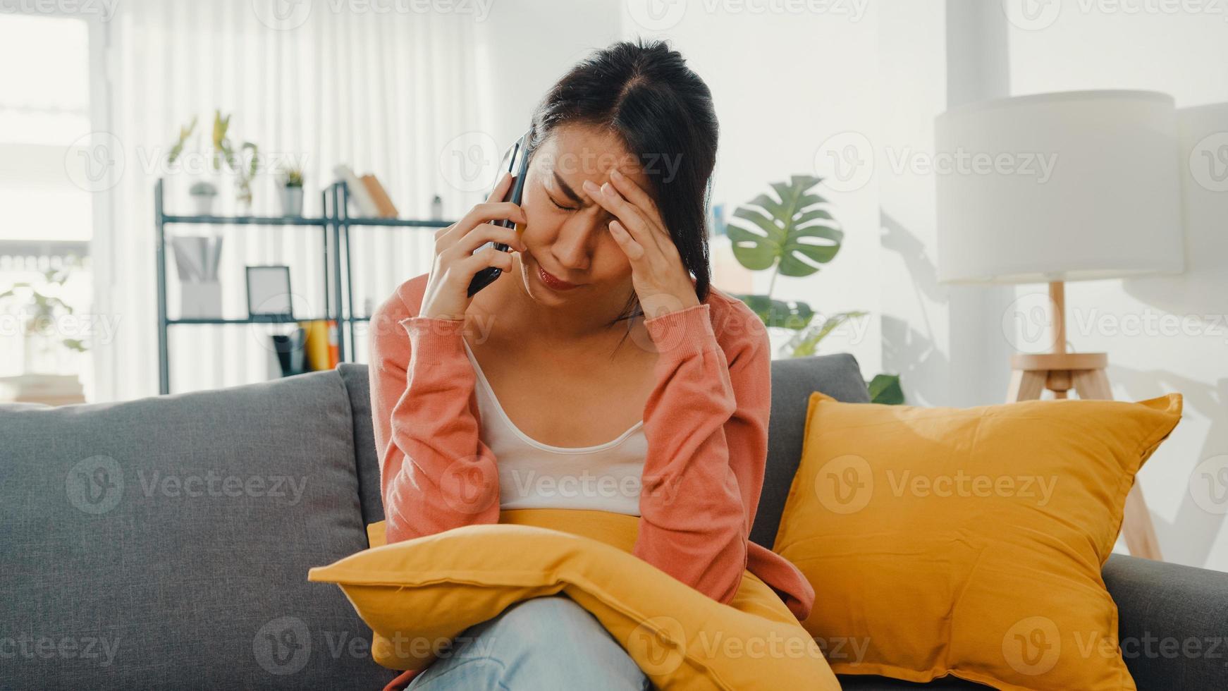 jovem sentada no sofá conversa com um amigo e recebe más notícias em casa. relacionamento de longa distância, relacionamento ruim, problema de trabalho, relacionamento rompido, manter distância, conceito de quarentena cobiçado. foto