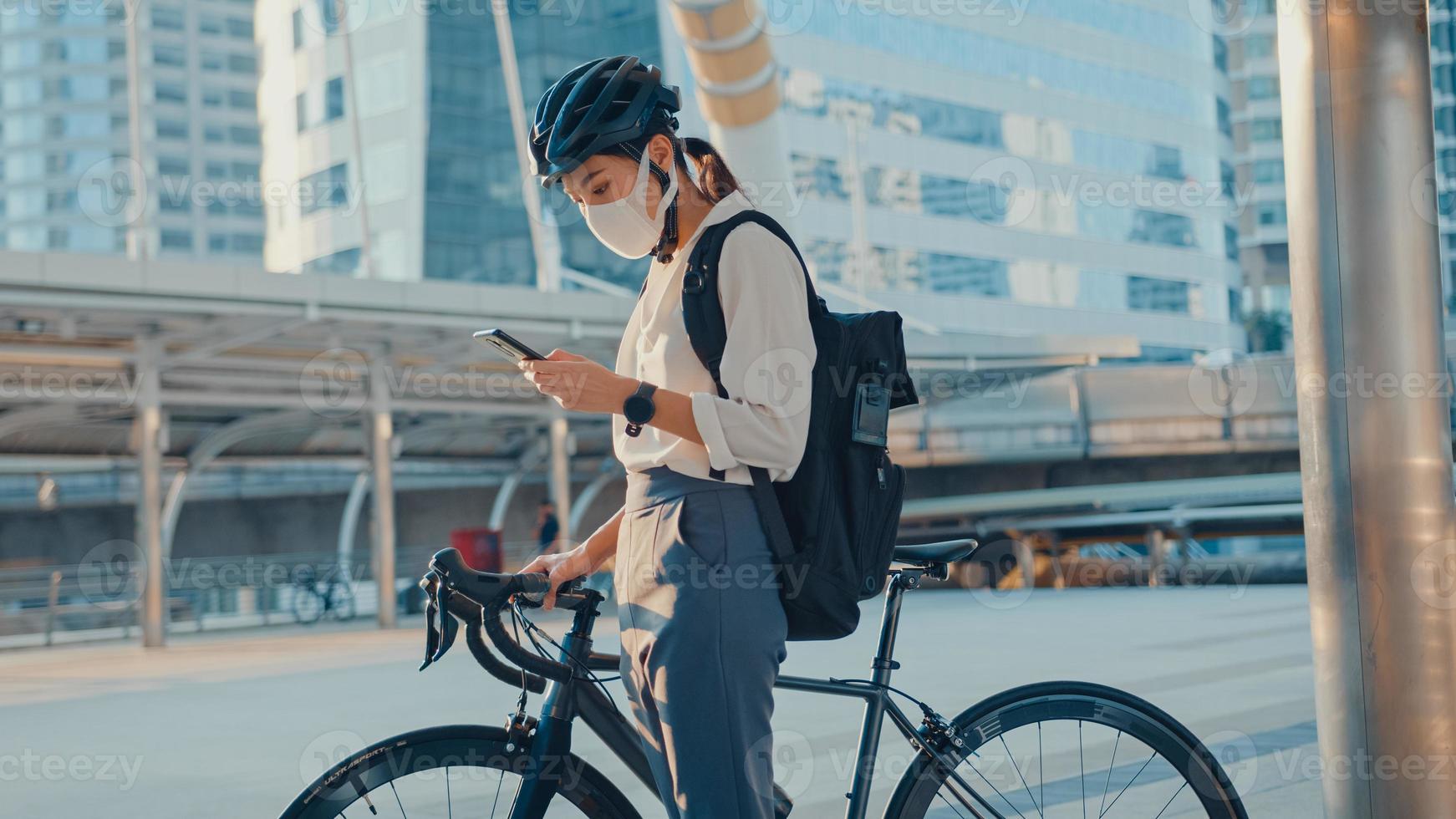 empresária asiática carregar mochila usar máscara de proteção antivírus dar uma caminhada de bicicleta e verificar o telefone na rua da cidade ir trabalhar no escritório. comutar para o trabalho, comutador de negócios para o conceito covid-19. foto