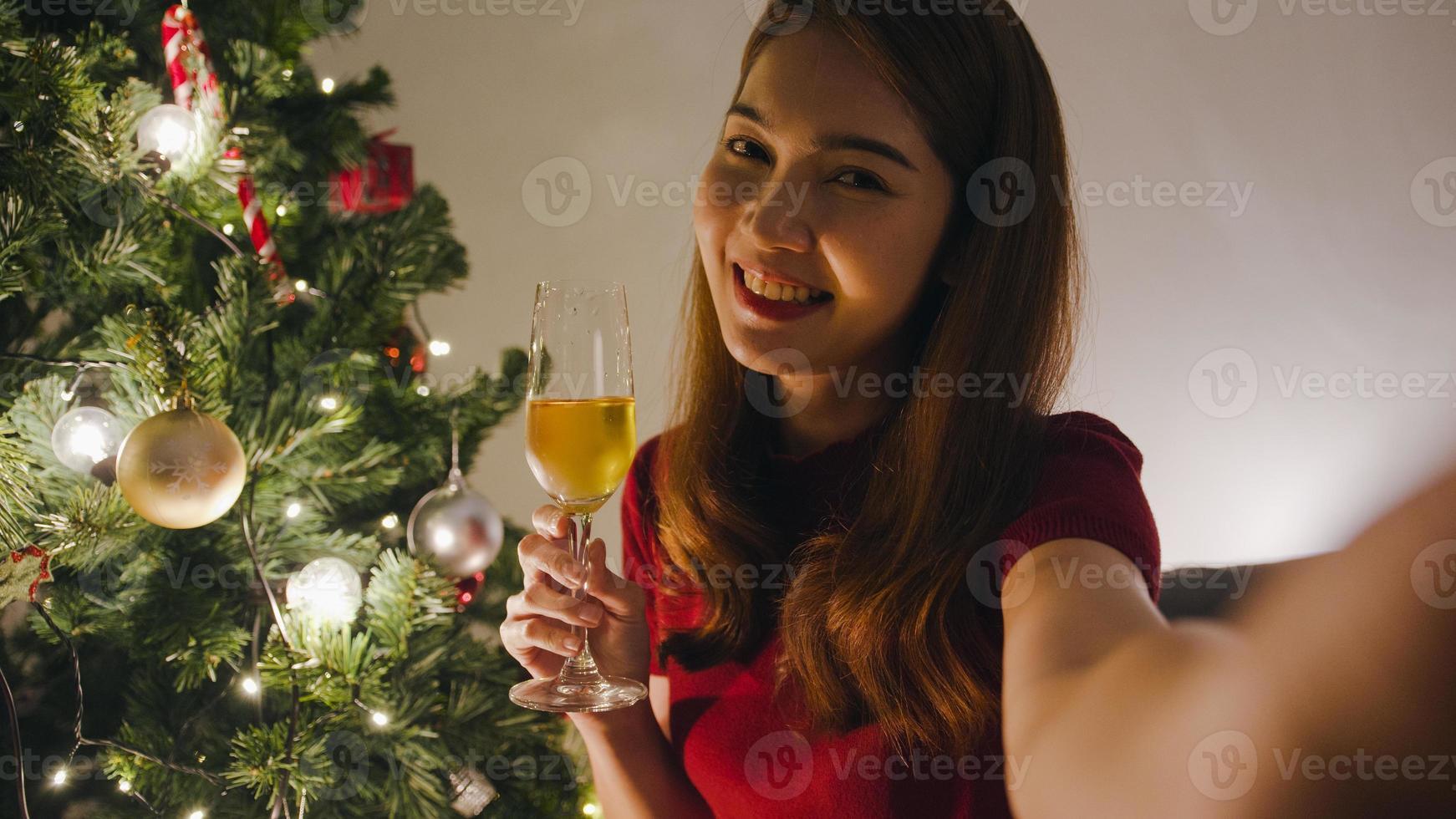 jovem ásia fêmea bebendo vinho se divertindo feliz noite festa videochamada com casal, árvore de natal decorada com enfeites na sala de estar em casa. noite de natal e festival de feriado de ano novo. foto