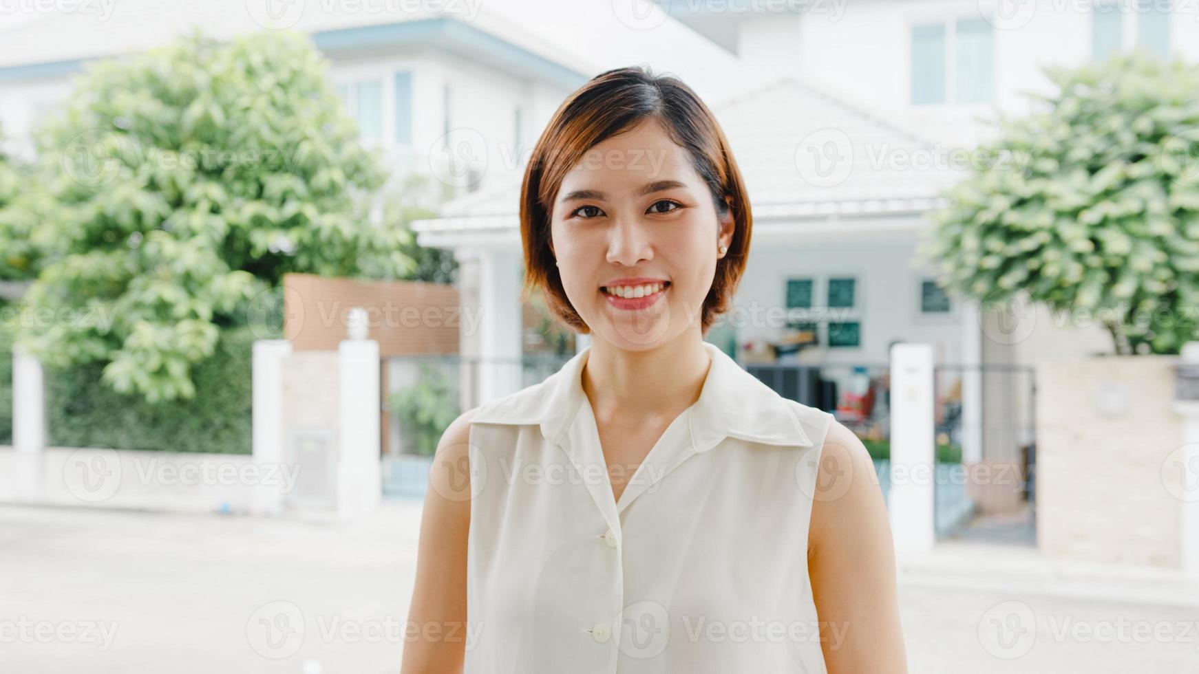 feliz jovem mulher asiática se sentindo feliz sorrindo e olhando para a câmera enquanto relaxa na rua na cidade moderna. mulher de estilo de vida fora do conceito de casa. foto