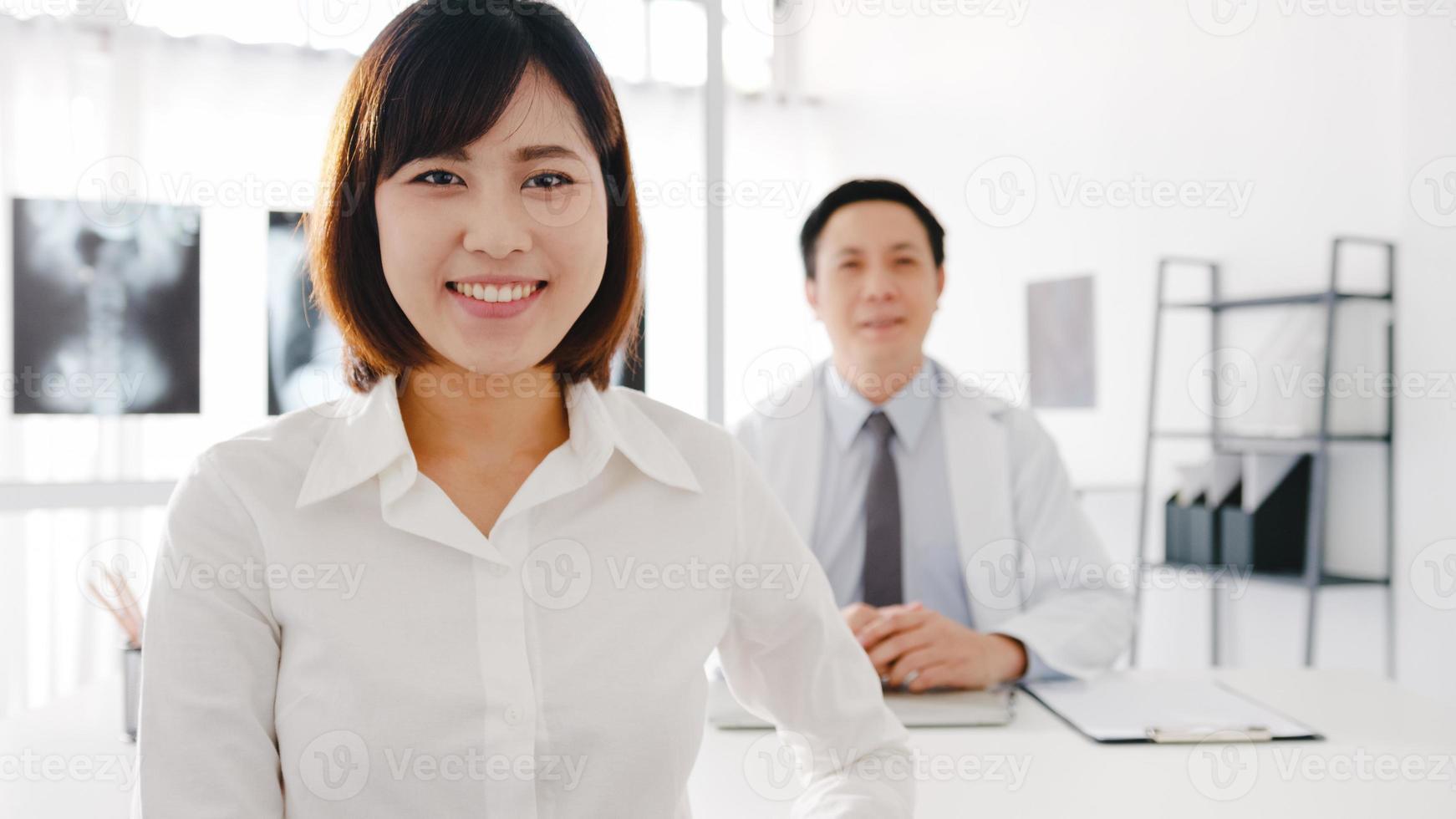 confiante asiático médico masculino em uniforme médico branco e jovem paciente olhando para a câmera e sorrindo enquanto consulta médica na mesa de clínica de saúde ou hospital. conceito de consultoria e terapia foto
